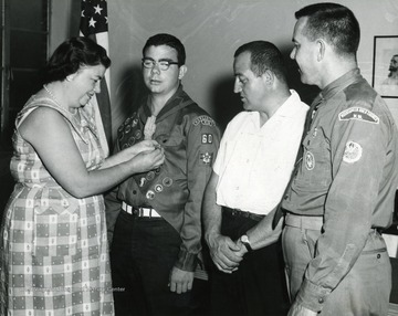 Mrs. Hartley (left) is pinning a medal (likely an Eagle Scout award) on her son.  Robert Hartley and Rev. LeJeune Lewis (far right) watch.