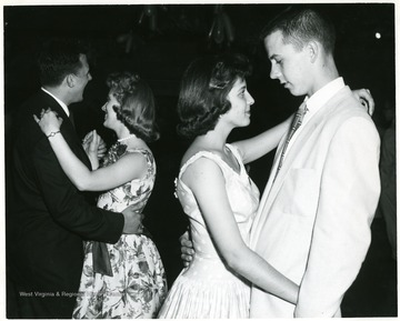 Two couples dance at the annual high school dance.