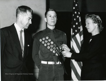 Mrs. Garlow pins an Eagle Scout award onto son David's sash while his father John looks on.