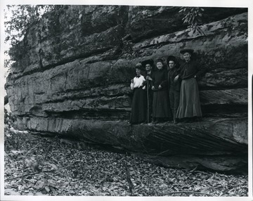 Couples pose for a photograph on a ledge. Possibly at Coopers Rock.