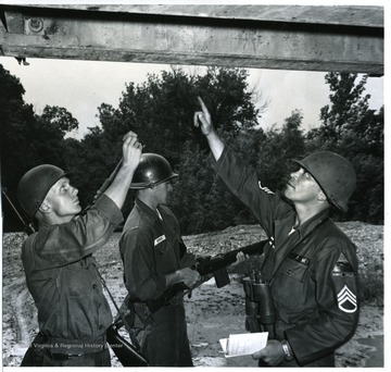'Basic Unit Training B Troop, 1st Recon Sqdrn, 1st Trng Bde. Classification of bridge to determine weight limit. Left to right: Private Charles F. Taplin of Cleveland, Ohio, Private Melvin E. Nichols of Santiago, California, and S/Sgt Romie Harmon of Morgantown, West Virinia.'