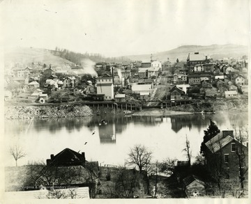 'View of Morgantown from the west side; Walnut Street Wharf; Old Firehouse in the upper end of Walnut Street, from the picture of the Wool Market was most likely made; Tower of Monongalia Academy at the left of the Firehouse. The negative for this picture was made by John L. Johnston, probably in 1892 or soon after. This twenty percent enlargement was made by F.A. Molby from the old negative (1939).'