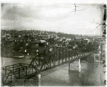 People can be seen crossing the bridge which spans the Monongahela River leading into Morgantown, W. Va.