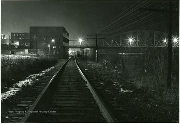 View of the railroad tracks during the night hours. 'John Foster'.