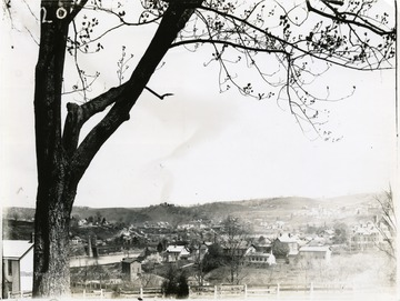 'Cameraman was near the DeMain Building on west side of South High Street near the bridge. Showing the Judge Dille property far in the background. The house at the end of the bridge was formerly the property of the late Henry L. Cox, father of Judge Cox. This house was moved about 300 yards up the hill and is now standing in good condition. Note the old Arnett hotel near the west end of the bridge. Shows Mechanical Hall by R. R. and J. W. Wiles house on Highland Avenue. Must have been about 1897.'
