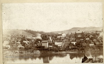 'Morgantown from across the Monongahela River sometime in the late eighties. Note unpaved Walnut Street and the River Wharf. To the left of which can be seen the bell tower on Old Monongalia Academy then used for the public school, and the old Fire Shed jutting out into the street. Property of Jas. R. Moreland.'