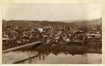 'Morgantown from across the Monongahela River. Sometime in the late eighties. Note this is the suspension bridge the Confederates partly burned during the Jones-Imboden raid in the Civil War. Property of Jas. R. Moreland.'