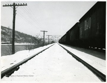 Tracks running along the Monongahela River and railroad cars on the right of the tracks.