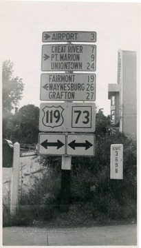 Highway signs to the airport, Cheat River, Point Marion, Uniontown, Fairmont, Waynesburg, and Grafton at the Intersection of Spruce St. and Willey St., Morgantown, W. Va.