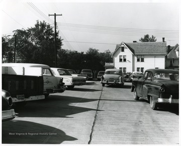 View of cars in the parking lot on the corner of Spruce and Pleasant St. Morgantown, W. Va. with Hastings Funeral home, formerly Hardigans Hospital.