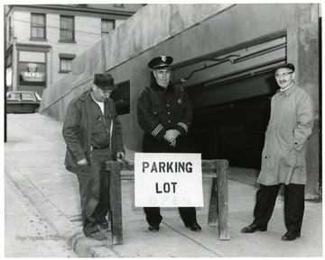 View of Parking garage entrance on Pleasant St. with workman (left to right) Harry Franks, Chief John Lewis, and Milton Cohen standing behind a sign.
