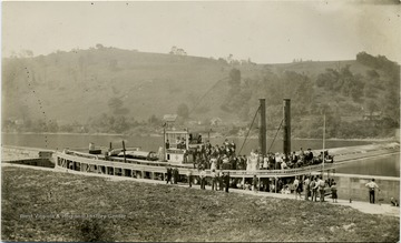 Passengers gathered on the deck of a steamboat on the Monongahela River.