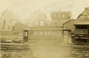 Man standing on the tracks next to a trolley in Morgantown. 'Photo found in city directory.'