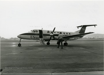 US Air Express 'Beechcraft 1900c' on the Hart airfield, and a man walking toward the plane.