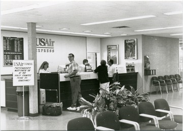The check in counter for USAir Express in Hart Field Airport.  Behind the counter is USAir employee, Joan Leach.