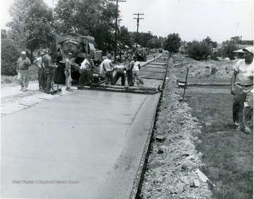 A group of men paving a street in Suncrest.