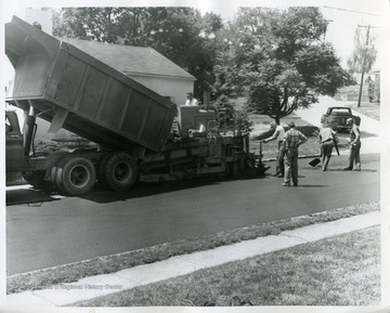 Men paving a street in Suncrest.