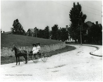 Two women in a horse and buggy travel on Willey Street.