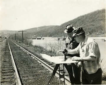 Men standing with surveying equipment next to the Baltimore and Ohio Railroad tracks and the Monongahela River.