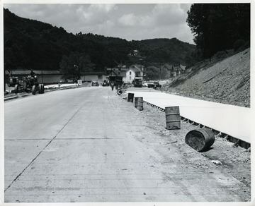 'Looking toward Morgantown on US 119 improvement. A relocation project for US 119 south of Morgantown is scheduled for completion this summer. Pictured is a northward look at paving work being done by Harman Brothers of Grafton, which was awarded the US 119 contract April 6, 1964, on a qualified low bid of $1, 596,255. Besides construction of 0.86-mile of US 119, the project includes a new Cobun Creek bridge.'