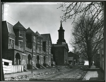 View of brick row houses and Methodist Episcopal Church 'now Cohen's Furniture' on Pleasant St before it was paved in Morgantown W. Va.