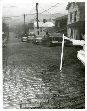 A man is measuring depth of street brick subsidence on North Spruce Street in Morgantown, West Virginia.