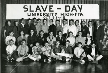 Group portrait of students on the FFA 'Slave - Day' at University High School October 9, 14-15, year unknown.  Students in the front row holding saws, wrenches, shovels, and axes.