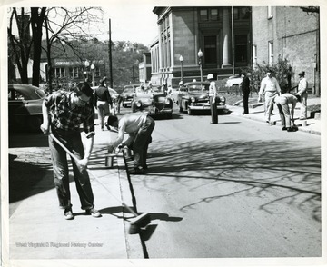Construction workers are working at the corner of High and Spruce Streets in Morgantown, West Virginia. 'Lower left: John Mollennex, West Virginia University student from Elkins. The Post Office is in the background.'