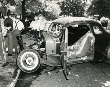 Veiw of a small car after it collided with a tree. Includes: 'David Spacht, Patrick Gilbert'
