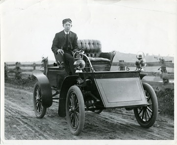"Fourtney Wade is sitting in a Grout steam automobile on Wilson Avenue in Morgantown.The Grout cars were originally sold under the ""New Home"" name in the 1890s, before rebranding as Grout Brother Automobiles after switching from internal combustion engines to steam powered cars. 1903 was their best sales year."
