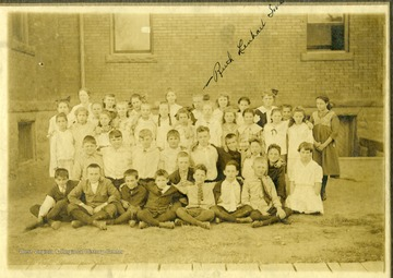 Class portrait of children outside of Seneca Elementary School.  Identified in the back row is Ruth Lenhart Smith.