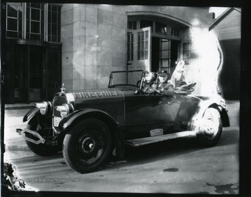"The car, which reads ""Fire Chief,"" is parked in front of the Morgantown Fire Department building on Spruce Street.  Doc, the fire department mascot, is in the backseat of the car."