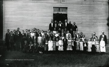 A photo of a large group of people in front of the M. E. Church.