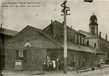 Several people stand in front of the Old Market House where the city building now stands in Wellsburg, W. Va.