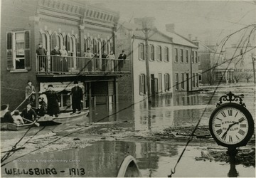 A flood on Main Street in Wellsburg, W. Va. People in row boats and on second story porch at left.