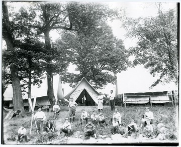 Campers sitting in front of tents holding various recreational equipment including guns, fishing pole, tennis racket, baseball bats, and oars.