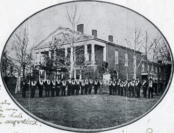 Group portrait of the Wapacoma Temperance Society meeting a Romney Literary Society. 'The building was erected in 1815 and is one of the first Literary Societies in the United States. It still constitutes a central part of West Virginia Schools for the Deaf and Blind. The building was donated in 1870 to the state of West Virginia as a school for the deaf and blind.'