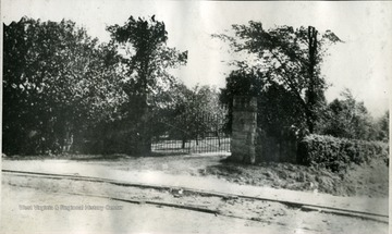 'This is the Point Breeze Gate. Down to the right (this side the hedge) runs the road to Wheeling,  through the farm and past the barns. The tracks of the street car line from Wellsburg to Bethany are seen in the foreground. This side the tracks is the virtified brick road, a state highway between the two places.'