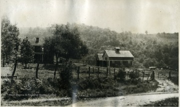 'This is a tennant house with barns on the left used for housing machinery and hogs. The trees faintly seen in the background are in large part Point Breeze woods across Buffalo creek. The road is the one to Wheeling. The picture is taken from the cow barn.'