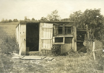 'Poultry house on the farm of Mr. W. L. Ball, R.F.D.2., Ravenwood. Mr. Ball keeps 100 hens in this house and a log poultry house of about the same size. Note the hen on the nest under the shed at the right of the house.' From photo album labeled 'Stewart A. Cody, County Agent, Jackson County, 1912.'
