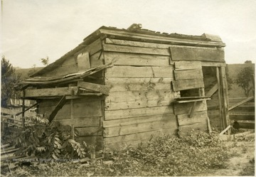 'Poultry house of Mr. W. R. Glovers, R.F.D. 2, Millwood. Twenty-seven fowls exist in this 8'x13' shed. The nest are constructed on the outside of the house, undoubtedly because of the preference of the hens.' From photo album labeled 'Stewart A. Cody, County Agent, Jackson County, 1912.'