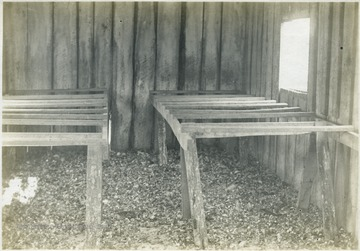 'Interior of Mr. C. E. Crow's poultry house. The perches are well arranged, the ventilation is fair, the house is well constructed, but the value of the poultry manure as a fertilizer is not considered. This is a general condition in certain parts of the county.' From photo album labeled 'Stewart A. Cody, County Agent, Jackson County, 1912.'