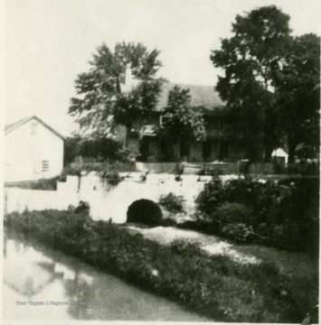 Old C&O Canal, and in the background the old Knode home, practically destroyed by the flood of 1936.