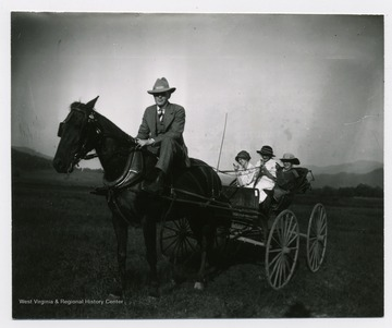 Three girls in the buggy, while a man rides the horse.