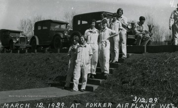 Group portrait of the women workers from Fokker Plant posing on the steps outside.