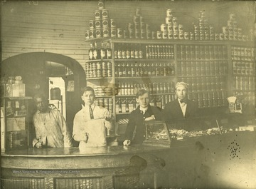 Olie, second from left, stands behind a counter sharpening a knife at Matoaka. An African American man stands to his right, and to his left are two other young men who also work at the store.