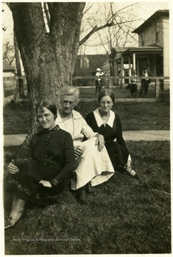 Photograph of Margaret, May, and Helen Ballard sitting outside together.