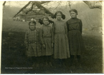 Photograph of Leah Reed, Helen Ballard, Maggie Ballard, and Mary Reed 'in order from left to right' on a postcard.