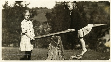 A postcard photograph of Maggie and Helen Ballard on a seesaw.