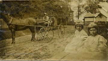 Collie Everman sits in a buggy with 'Dan'. Maggie and Helen Ballard sit at the side of the road in the foreground.